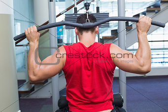 Strong bodybuilder using weight machine for arms