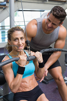 Female bodybuilder using weight machine for arms with encouraging trainer