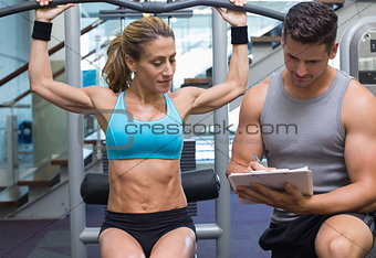 Female bodybuilder using weight machine for arms with trainer taking notes