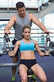 Personal trainer coaching female bodybuilder using weight machine