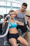 Personal trainer coaching smiling female bodybuilder using weight machine