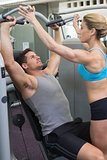 Personal trainer coaching bodybuilder using weight machine