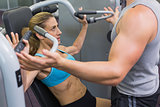 Personal trainer coaching female bodybuilder using weight machine