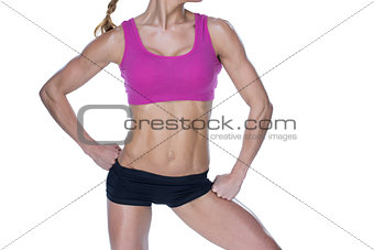 Female bodybuilder posing in pink sports bra and shorts mid section