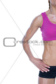 Female bodybuilder posing with hand on hip with copy space