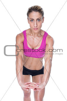Female bodybuilder flexing with hands together looking at camera