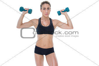 Female bodybuilder holding two dumbbells with arms up