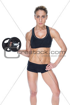 Female bodybuilder holding large black dumbbell with arm up looking at camera