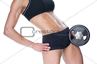 Female bodybuilder holding large black dumbbell mid section