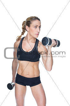 Female bodybuilder working out with large dumbbells