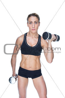 Female bodybuilder working out with large dumbbells looking at camera