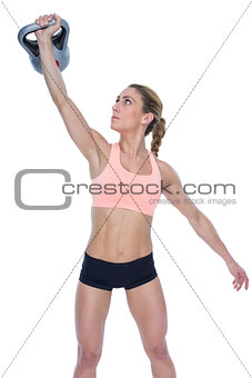 Female crossfitter lifting up kettlebell
