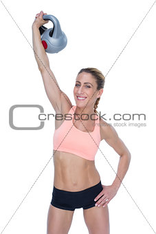 Female blonde crossfitter lifting kettlebell above head smiling at camera