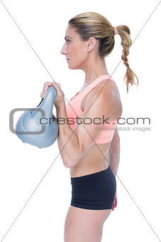 Female blonde crossfitter lifting kettlebell