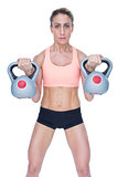 Serious female crossfitter lifting kettlebells