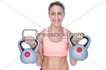 Smiling female crossfitter lifting kettlebells