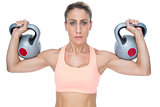 Serious female crossfitter lifting kettlebells looking at camera