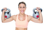 Happy female crossfitter lifting kettlebells looking at camera