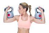 Strong female crossfitter lifting kettlebells