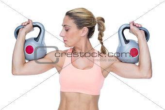 Strong female crossfitter lifting kettlebells