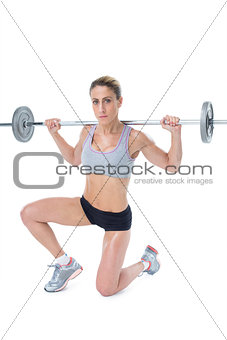 Strong female crossfitter lifting barbell behind head looking at camera