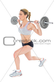 Serious female crossfitter lifting barbell behind head