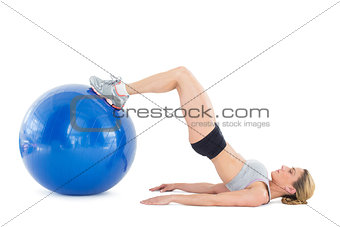 Fit woman lying on floor with legs on exercise ball