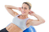 Fit woman doing sit ups on blue exercise ball smiling at camera
