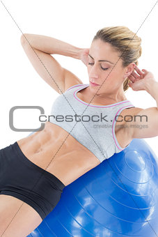 Fit woman doing sit ups on blue exercise ball