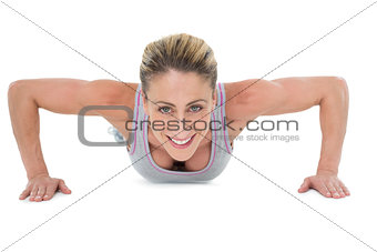 Strong woman doing press ups smiling at camera