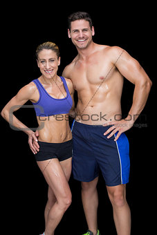 Crossfit couple smiling at camera with hands on hips