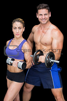 Crossfit couple posing with dumbbells smiling at camera