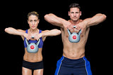 Crossfit couple posing with kettlebells