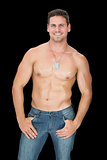 Handsome muscular man posing in blue jeans smiling at camera