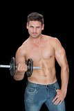Muscular man lifting dumbbell in blue jeans