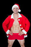 Smiling muscular man posing in sexy santa outfit