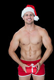 Smiling muscular man posing in sexy santa outfit holding gift