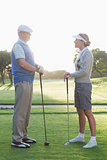 Golfing couple standing and talking