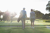 Golfing couple walking and chatting