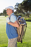 Golfer standing holding his golf bag