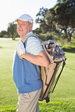 Golfer standing holding his golf bag smiling at camera