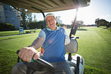 Golfer driving his golf buggy and smiling at camera