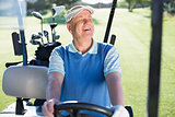 Happy golfer driving his golf buggy