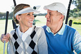 Happy golfing couple sitting in golf buggy smiling at each other