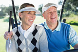 Happy golfing couple sitting in golf buggy smiling