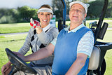 Happy golfing couple sitting in golf buggy looking around