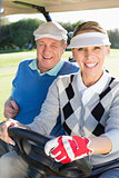 Happy golfing couple sitting in golf buggy smiling at camera