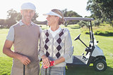 Happy golfing couple with golf buggy behind
