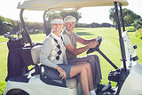 Happy golfing couple sitting in buggy smiling at camera