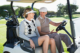 Happy golfing couple sitting in buggy smiling at each other